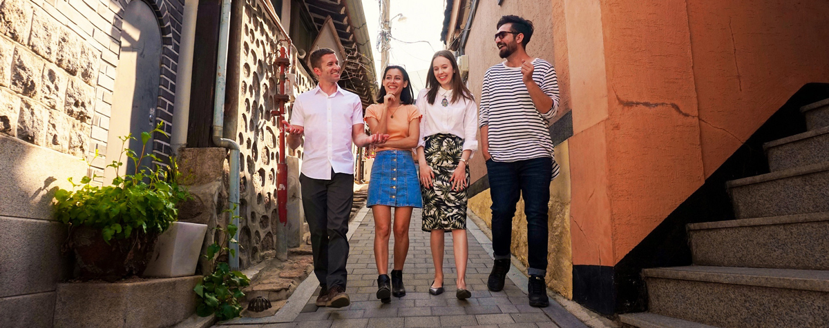 Four friends walking  down a narrow cobblestone street in an old village