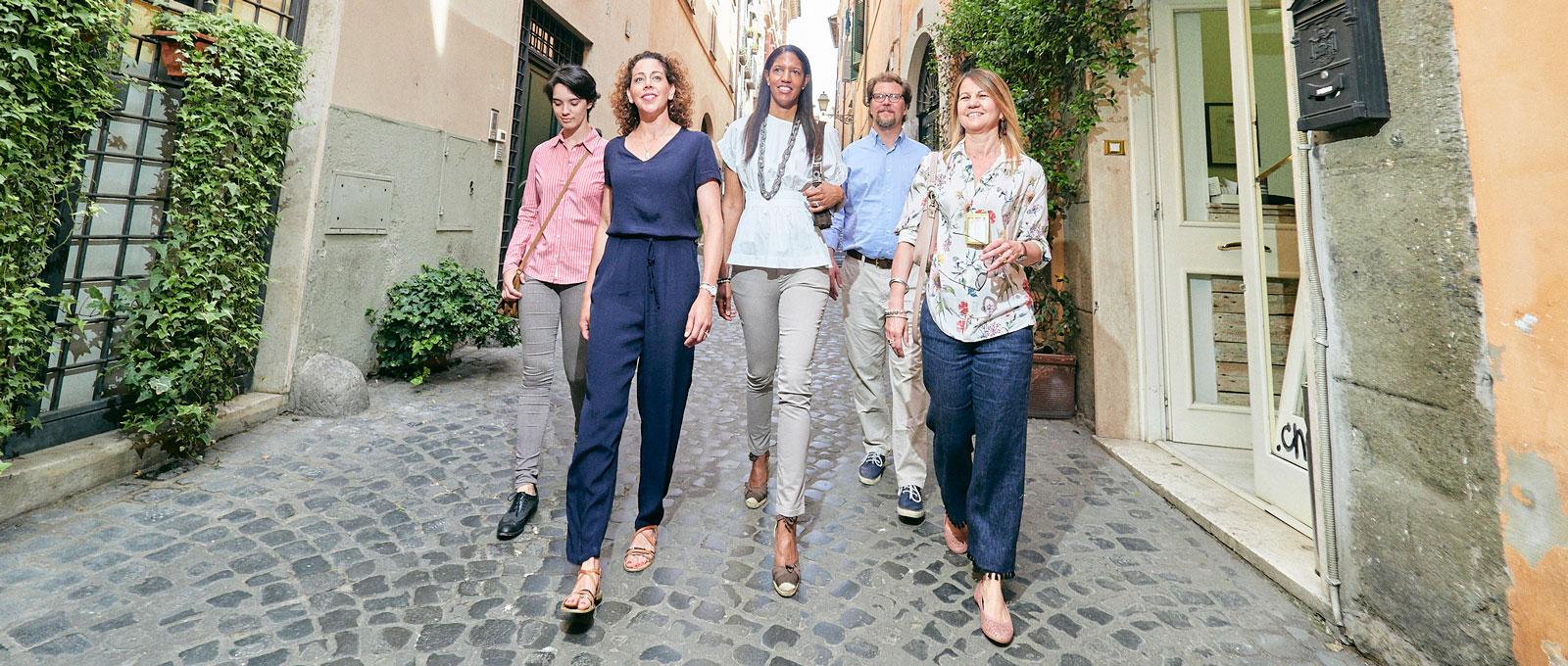 Four friends walking  down a narrow cobblestone street in an old village